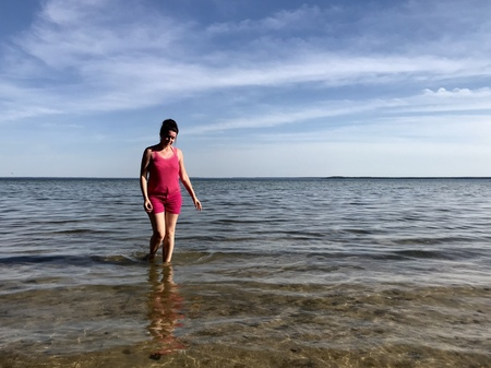 The girl walks through the water in shallow water off the shores of the lake.  Visible clear water and beautiful blue sky.