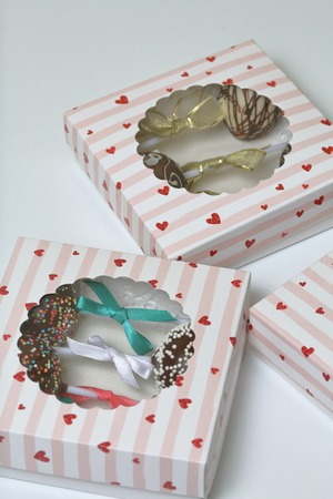 Cake pops decorated with a bow of braid, packed in a gift box. In the lid of the box is a transparent window.