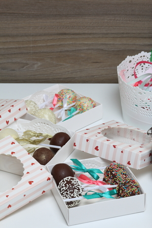 Cake pops decorated with a bow of braid, packed in a gift box. Nearby a container with tapes of different colors.