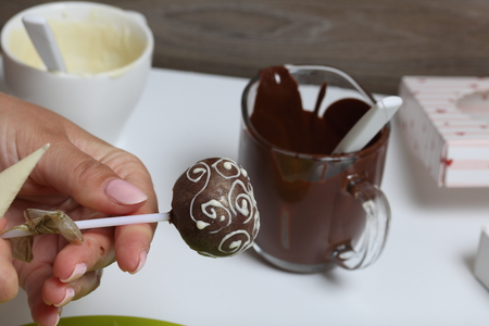 A woman decorates with the help of white chocolate popcake glazed with dark chocolate.