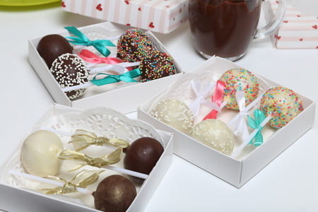 Cake pops decorated with a bow of braid, packed in a gift box. Nearby are cups of melted chocolate. Stockfoto