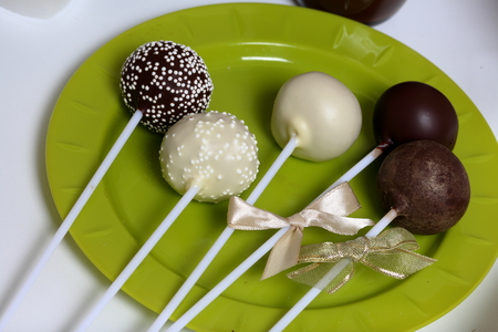 Cake pops decorated with a bow of braid are on a plate. Stockfoto