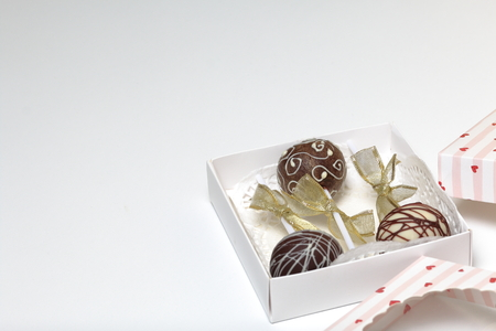 Cake pops decorated with a bow of braid, packed in a gift box. Stockfoto