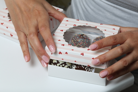 Cake pops decorated with a bow of braid, packed in a gift box. Woman closes the box.