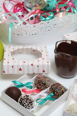 Cake pops decorated with a bow of braid, packed in a gift box. Nearby are cups with melted chocolate and a container with tapes of different colors. Stockfoto