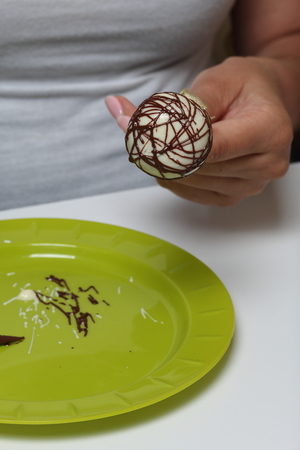 A woman decorates with the help of dark chocolate popcake glazed with white chocolate. Stockfoto
