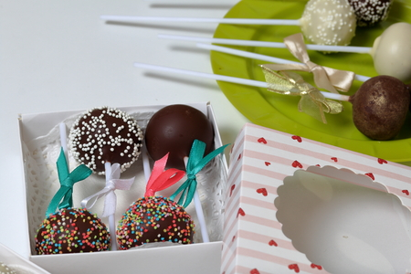 Cake pops decorated with a bow of braid, packed in a gift box. Other sweets are close by on the plate.