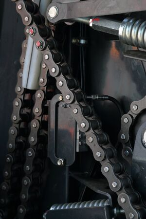 Transmission agricultural machinery. Sprockets, chain drives and springs are visible. Close-up.