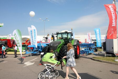 MINSK, MINSK, BELARUS 6 JUNE 2019, Exposition at the exhibition BELAGRO 2019. A mother with a child in a wheelchair looks at the exhibits. Redakční