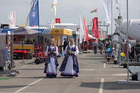MINSK, MINSK, BELARUS 6 JUNE 2019, Exposition at the exhibition BELAGRO 2019. Visitors are passionate about viewing. Girls in national costumes.