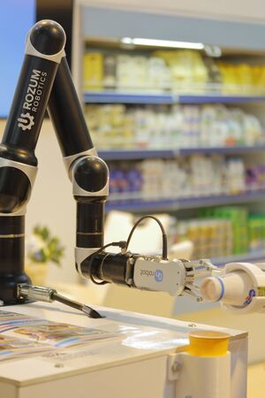 MINSK, MINSK, BELARUS 6 JUNE 2019, Exposition at the exhibition BELAGRO 2019. Food industry products. The robot pours yogurt from a bottle into a glass.