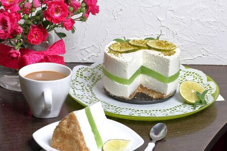 Lime cheesecake without baking. The piece is cut off. Lies on a plate. Near a cup of coffee with milk. In a glass vase is a bouquet of roses. Against the background of white wall with decorative plaster. Reklamní fotografie
