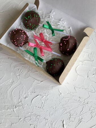 Cake pops decorated with a bow of braid, packed in a gift box.  On the surface covered with decorative plaster white.