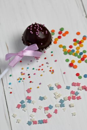 Cake pops decorated with a bow of braid. They lie on the boards, painted white. Nearby is scattered multicolored decorative topping.