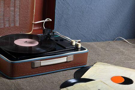 Un vieux gramophone avec un disque vinyle monté dessus. À côté des enveloppes en papier minables se trouvent d'autres documents.