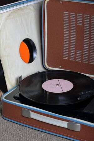 An old gramophone with a vinyl record mounted on it. Next to shabby paper envelopes are other records.