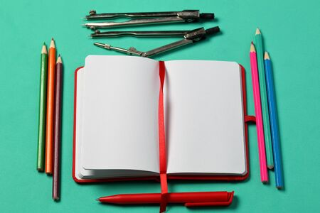 Notebook for notes in the red cover. With a red bookmark and pen. Lies opened on a mint background. Beside a set of colored pencils and accessories for drawing. School supplies.
