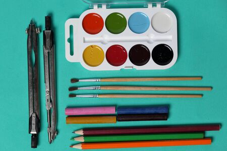 Accessories for drawing and sketching. Decomposed on the surface of mint color. School supplies. Stock Photo