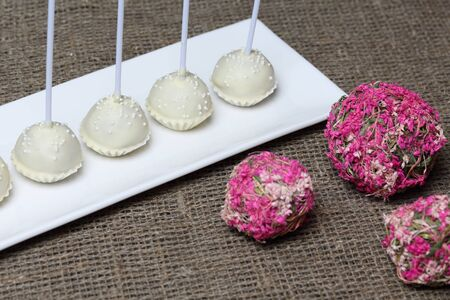 Cake pops in white chocolate glaze. Stand vertically on a stand. Decorated with white decorative sprinkles. Near rattan balls.