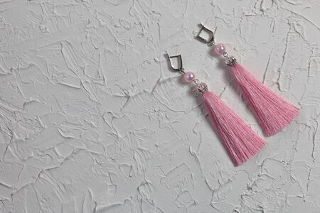 Earrings tassels. They lie on the surface covered with white decorative plaster.