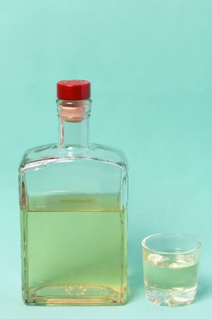 A bottle of strong alcohol. From transparent glass, a square form with a red stopper. Near a stack with a drink poured. Against the background of mint color.