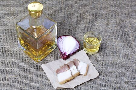 A bottle of strong alcohol. From transparent glass, a square form. Near a stack with a drink poured. On a piece of paper lies chopped bacon and onions. Against the backdrop of coarse linen fabric. Stock fotó