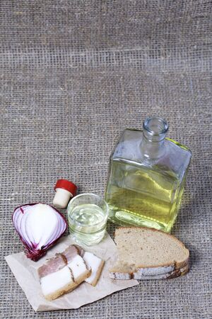 A bottle of strong alcohol. From transparent glass, a square form. Near a stack with a drink poured. On a piece of paper lies chopped bacon, bread and onions. Against the backdrop of coarse linen fabric.