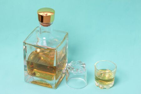 A bottle of strong alcohol. From transparent glass, a square form with a golden stopper. Near a stack with a drink poured. The second stack is turned upside down. Against the background of mint color.