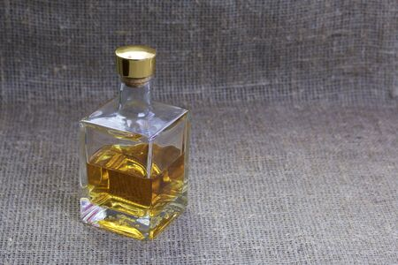 A bottle of strong alcohol. From transparent glass, a square form with a golden stopper. Against the backdrop of coarse linen fabric. Stock fotó