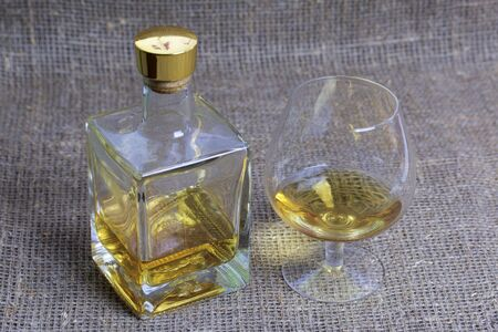 A bottle of strong alcohol. From transparent glass, a square form with a golden stopper. Near a glass with a drink poured. Against the backdrop of coarse linen fabric.