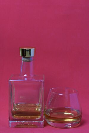 A bottle of strong alcohol. From transparent glass, a square form with a golden stopper. Near a glass with a drink poured. Against the background of coral color.