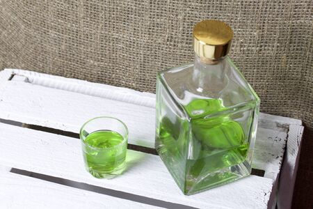 Strong tincture on tarhuna in a transparent rectangular bottle. Drink bright green poured into a glass.