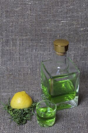 Strong tincture on tarhuna in a transparent rectangular bottle. Drink bright green poured into a glass. Next to the ingredients for cooking. Tarragon leaves and lemon.