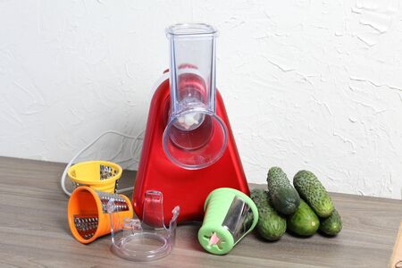 Vegetable cutter with various nozzles. Standing on the tabletop. Near cucumbers. Фото со стока