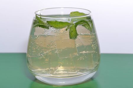 Refreshing drink with gas bubbles. Nalit in a transparent glass. It laid crushed ice. Decorated with mint leaves. Stock fotó
