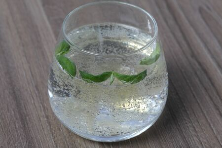 Refreshing drink with gas bubbles. Nalit in a transparent glass. It laid crushed ice. Decorated with mint leaves.