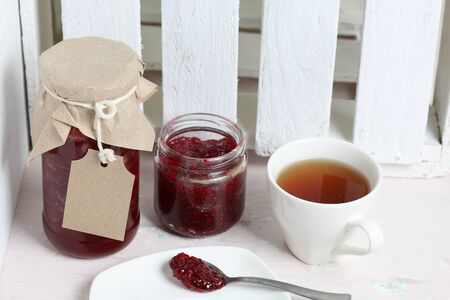 Jars of jam, covered with paper and tied with twine. On the string hang craft labels. One jar is open. Near a cup of tea.