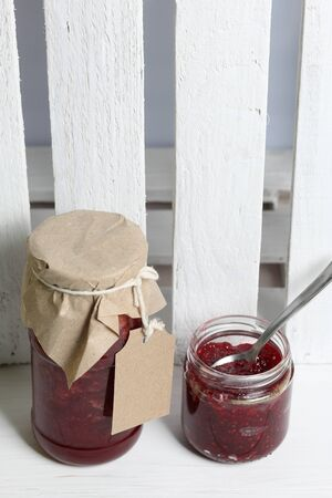 Jars of jam, covered with paper and tied with twine. On the string hang craft labels. One jar is open.
