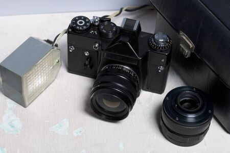 Old film camera, removable lens and wired flash. They lie on the surface of the table.
