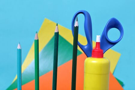 Color pencils in green shades. Scissors, glue and colored paper for application. They are located vertically.