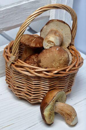 Wicker basket with porcini mushrooms. Nearby lies one mushroom. Near a box of boards.