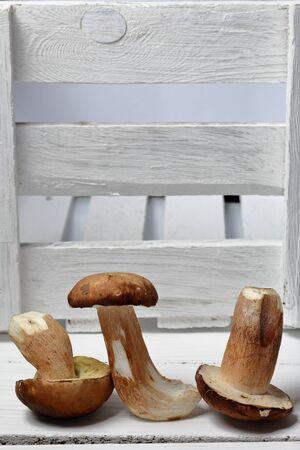 A few fresh porcini mushrooms. Near a box of boards.