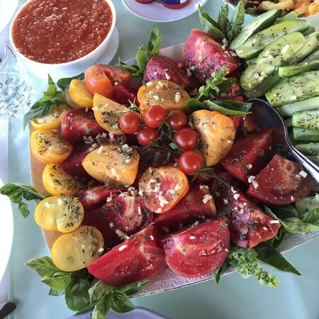 Many vegetables cut into pieces lie on a dish. Sprinkled with spices and garlic. Decorated with greenery. Holiday treat. Stock fotó