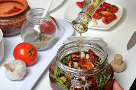 Sun-dried tomatoes with spices and garlic in a jar. Woman adds olive oil. Near rosemary, tomatoes and garlic. Stock fotó
