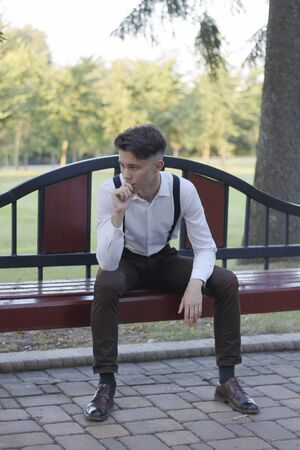 Stylishly dressed young man sits on a park bench. He looks away and laughs.