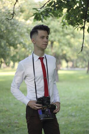 Stylishly dressed young man posing in a park. A SLR film camera hangs on the neck.