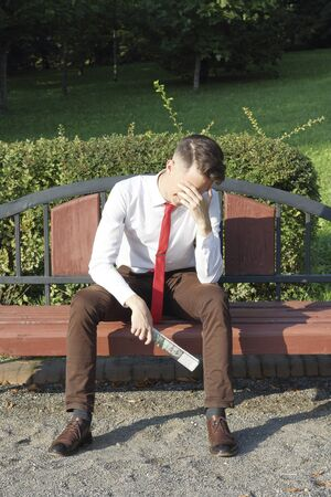 A stylishly dressed young man sits on a park bench and holds a newspaper in his hands. He covered his face with his palm. Stock fotó