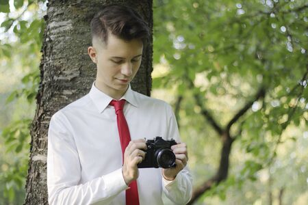 Stylishly dressed young man posing in a park. Holds the camera in his hands and works with the settings. Stock fotó