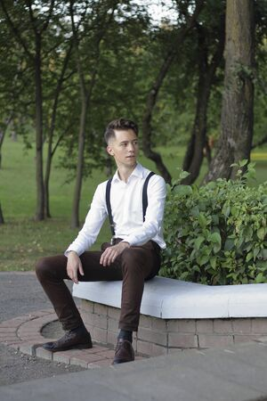 Stylishly dressed young man posing in a park. Sits on the curb and looks away.