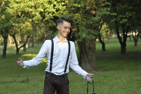 Stylishly dressed young man posing in a park. Laughing makes a helpless gesture.